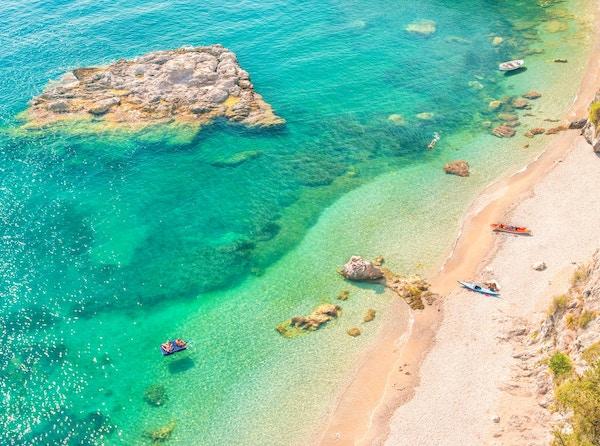 flyfoto av flere mennesker som hviler på vill bortgjemt strand med turkisblå vann på den varme solfylte sommerdagen