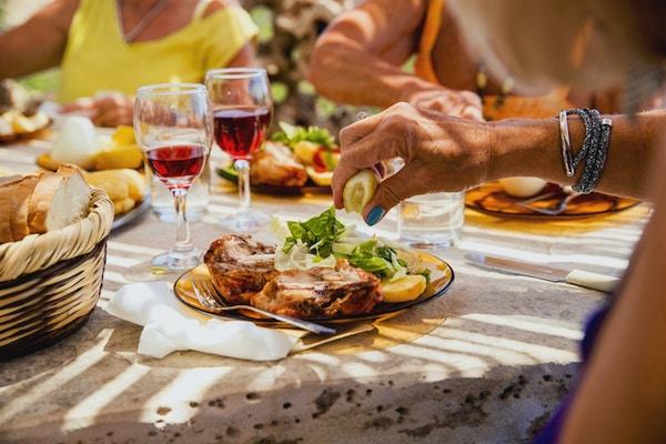 Lady koser seg med maten sin servert med en halv tallerken kjøtt og den andre halvparten salat. Hun blir sittende ved bordet sammen med vennene sine i restauranten på ferien.