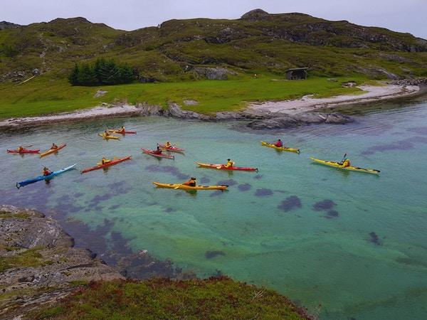 Mennesker sett ovenfra som padler i klart vann i fargerike kajakker med naturen rundt seg