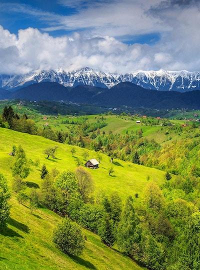 Fantastisk, alpint landskap med grønne åkrer og høye snødekte Piatra Craiului-fjell nær Brasov, Transylvania, Romania, Europa