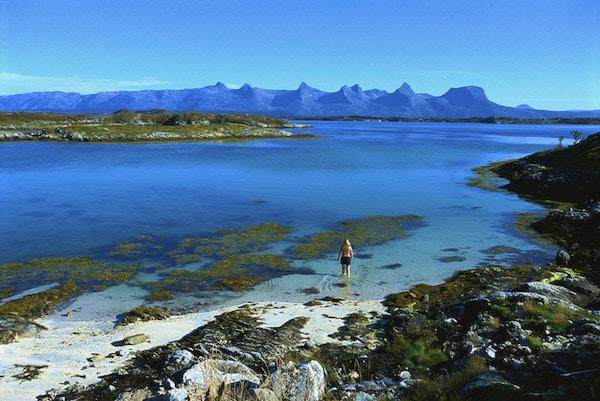 Dame som er på vei ut i det krystallklare vannet og hvit sand på Helgelandskysten med de syv søstre i bakgrunnen