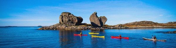 Fire kajakker på tur tatt på avstand slik at naturen og vannet er fremtredende. Det er en steinformasjon på siden