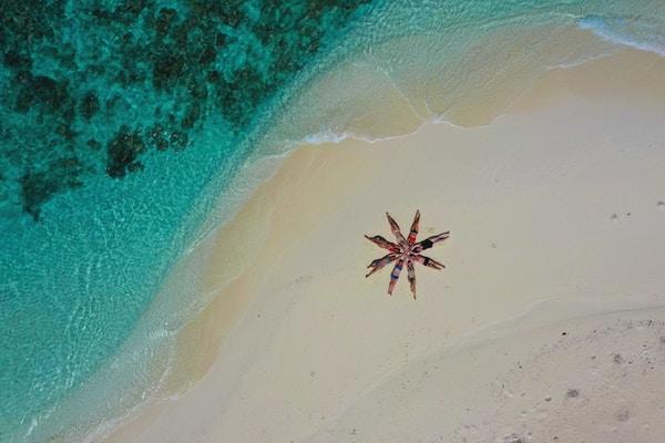 Mennesker på strand som ligger i sanden og danner en sjøstjerne