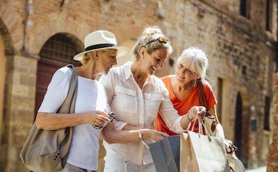 En kvinne står i en gammel del av byen i Italia og holder på med handleposer. Hun viser de to vennene sine hva hun har kjøpt. Alle tre smiler mens de står side om side