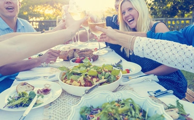 Gruppe av venner som spiser måltid utendørs. De feirer med en skål med vin. De er alle glade og smilende. Det er boller med mat på bordet, inkludert salat og spaghetti Bolognese. Multietnisk gruppe.