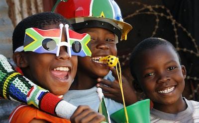 Tre afrikanske barn forbereder seg på å se verdensmesterskapet i fotball i Johannesburg, Sør-Afrika.