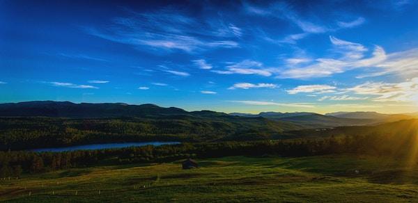 Landskapsbilde av Espedalen med en åpen slette foran en innsjø, grønne skogsområder og fjell i bakgrunnen