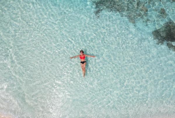 Kvinne som ligger i det klare  vannet med bikini og solbriller