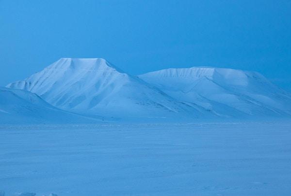 """""""Arktisk landskap under polarnatten i Spitzbergen Adventdalen nær Longyearbyen. I løpet av den arktiske natten mellom desember og januar er det 24 timer mørkt, men i klare netter med måneskinn eller nær soloppgang er det en typisk blå skumring. Nattskudd med lang tidseksponering! Rikelig med kopieringsplass, monokromt bilde. """""""