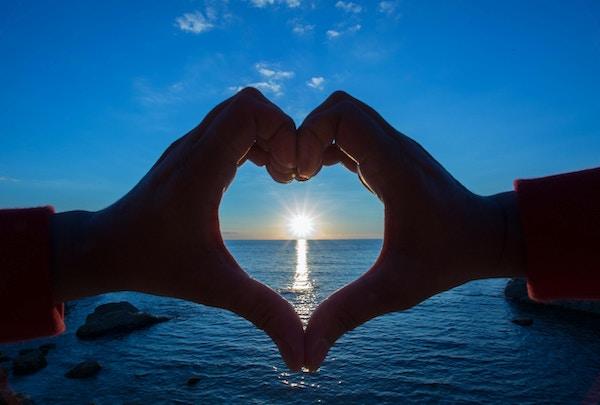 Hjerteform laget med hender som omslutter den kypriotiske morgensolen i horisonten.