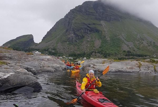 Jente i gul drakt og lue padler rød kajakk med fjell i bakgrunnen