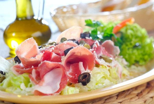 Aromatiske skiver av tørket prsutskinke, salt ost, oliven og syltet løk på de grønne salatbladene som er drysset i vinaigrette-saus
