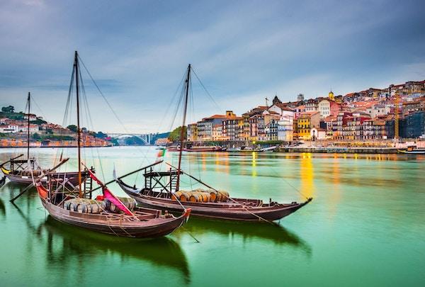 Utsikt over gamlebyen i Porto, Portugal, mot Douroelven med sine tradisjonelle Rabelobåter