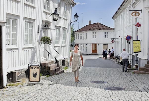 En kvinne går på brostein forbi en hvit bygning med museumsskilt utenfor