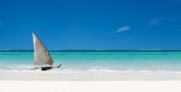 Seil båt i havet ved stranden med klar blå himmel og hvit sand