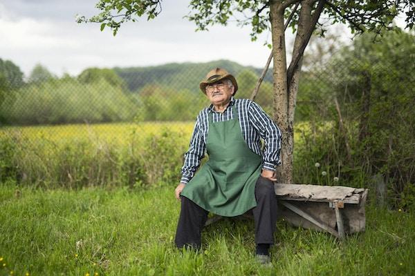 Portrett av selvsikker eldre bonde i hagen.