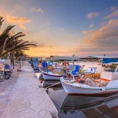 Gresk fiskehavn med båter, palmer og scootere ved soloppgang på en vakker, rolig sommerdag i juli