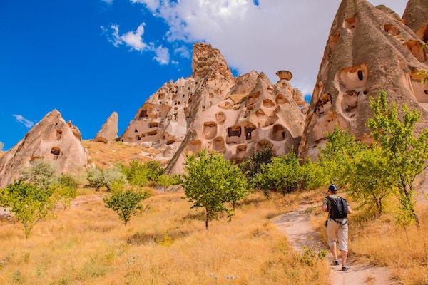 Ryggsekkturist på fottur blant hulesteiner i Cappadocia-området, sentrale Tyrkia.