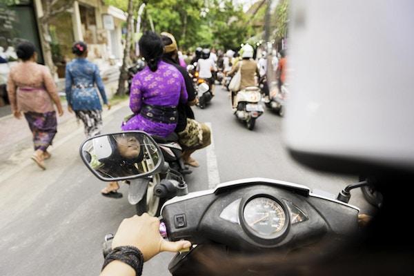 Dette over skulderfrie arkivfotografiet er fra motorsykkel bakre passasjer synspunkt. En 18 år gammel indonesisk kvinne kjører kjøretøyet. Hjelmen hennes er ute av fokus i forgrunnen og gir kopiplass. Veien videre i Ubud, Bali, er full av andre motorscootere og fotgjengere som har på seg fargerike, tradisjonelle balinesiske klær i løpet av sent på ettermiddagen. Fotografert med et Nikon D800 DSLR-kamera.