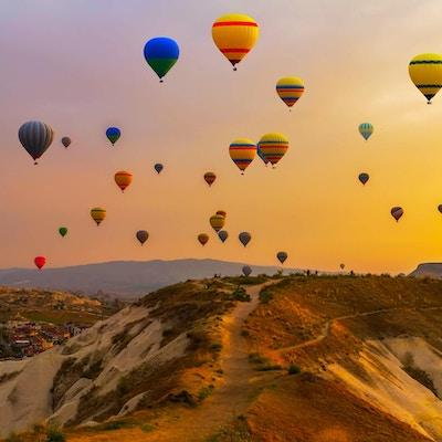 Luftballonger som lander i et fjell Cappadocia Goreme nasjonalpark, Tyrkia.