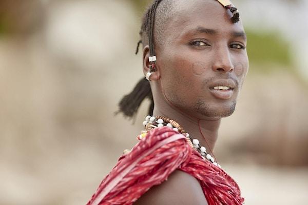 Elegant Maasai-mann som står under Zanzibars palmer.