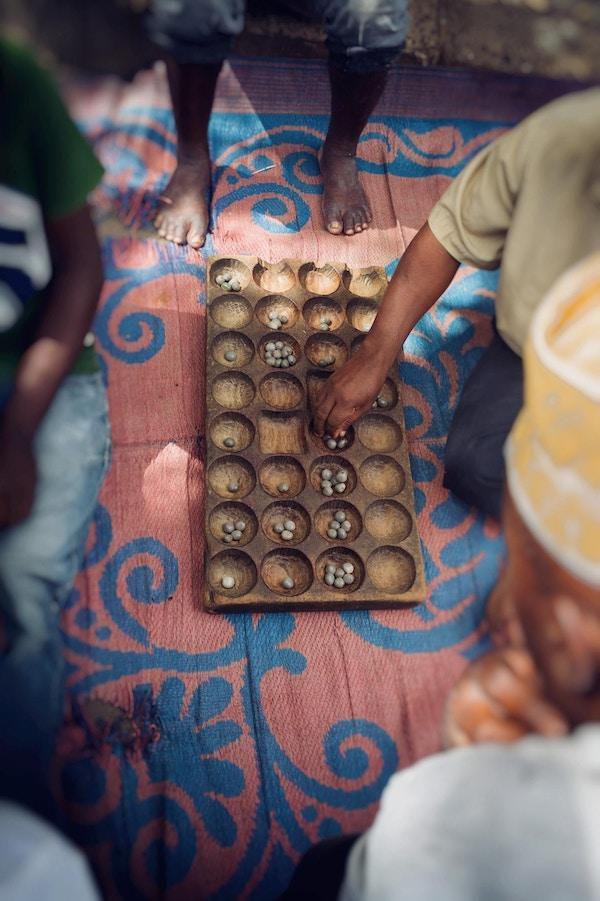 Bao Game som spilles av afrikanske menn på markedsgulvet fotografert rett over med fargerike matter for å sitte på Dar es Salaam Tanzania