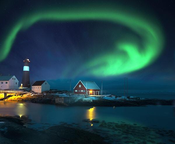Spektakulær form på nordlys (Aurora borealis) over fyrtårn ved sjøen om vinteren.