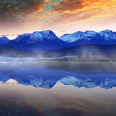 Vinternorsk landskap med hav og fjell under soloppgang
