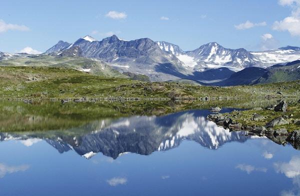 Refleksjon av fjellkjede i et lite hav i Jotunheimen nasjonalpark i Norge.