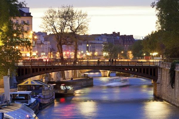Seine River & Pont au Double nær Notre Dame katedral i skumringen, Paris, Frankrike