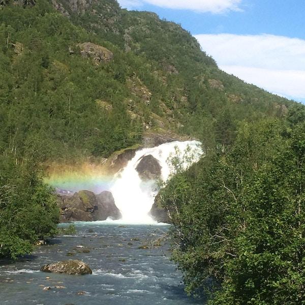 Regnbuefarger i luften foran et fossefall i Mørkrisdalen