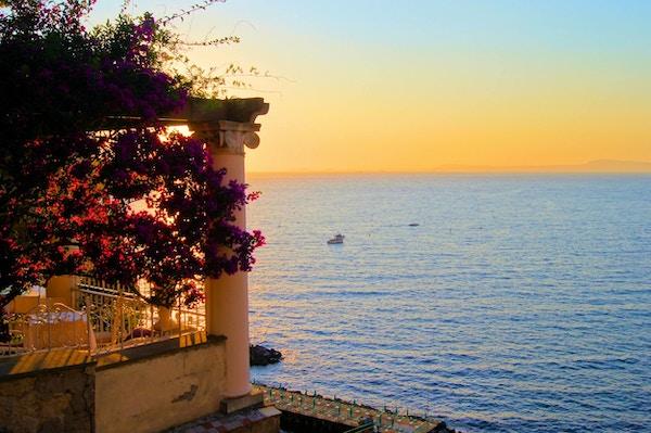 Utsikt fra Sorrento, Italia i skumringen fra en blomstringt terrasse