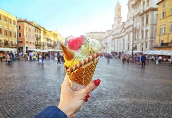 Italiensk iskrem holdt i hånden på bakgrunnen til Piazza Navona i Roma, Italia