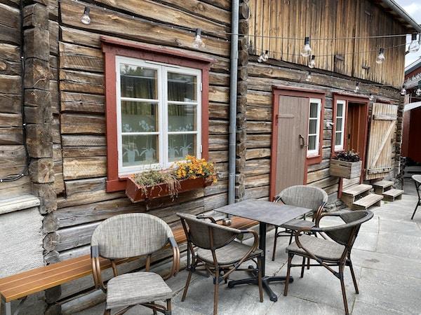 Stoler og bord foran trebygning med røde vinduskarmer