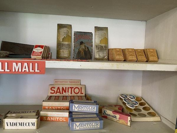 Varehylle fylt med et gammelt vareutvalg som vademecum, mentolin tannkrem, sanitol og tobakk