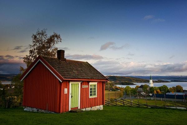 Lite rødt hus med grønn dør med kirken og fjorden i bakgrunnen