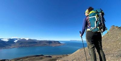 Kvinne med sekk som ser utover landskapet på Svalbard fra fjell