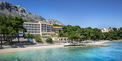Strandlinje  med lys sand og klart vann med hotellbygning i bakgrunnen og fjell bak der igjen