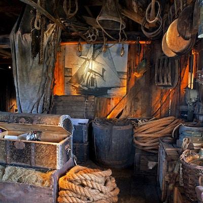 Gamle skipskister, rep og fiskeredskap henger i et eldre skjul