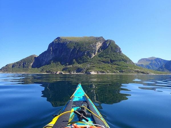 En blå kajakk glir frem på et speilblankt hav med holmer rett frem
