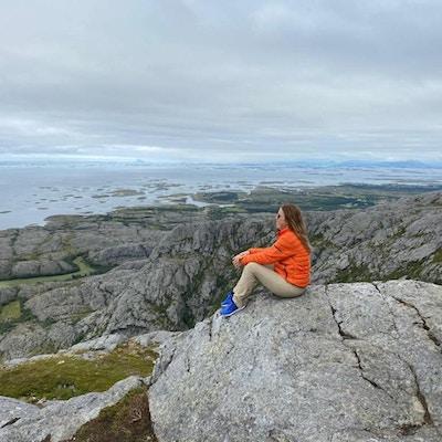 Kvinne i oransje jakke sitter på et fjell og ser utover havet