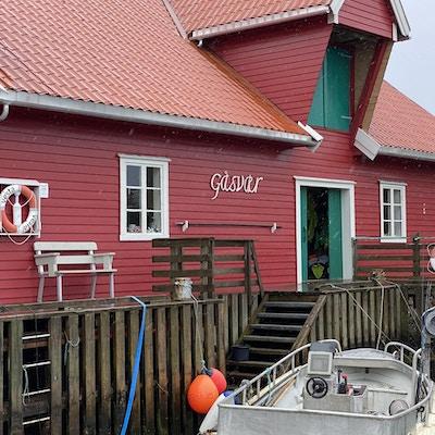 Rødt hus med Gåsvær på veggen, grønne skodder og grønn dør. Båt utenfor