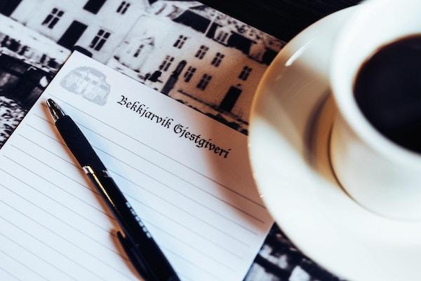 Papir med logo, penn og kaffekopp.