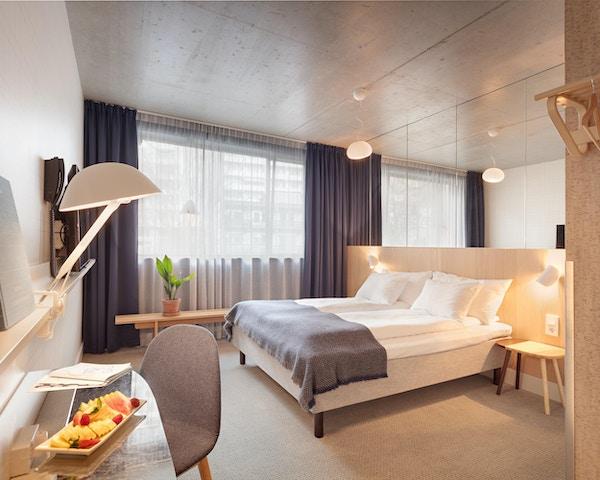 Hotellrom i duse farger med stor seng, stol, bord, lampe og fruktfat på bordet
