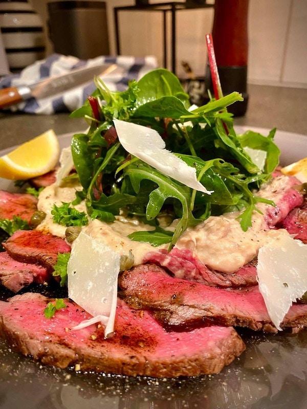 Et fat med rosastekt kjøtt i skiver med ruccola og parmesan og sitron ved siden av
