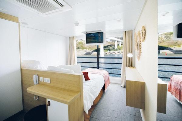 Lugar med teppe, seng, skap, tv og vindu. Foto.