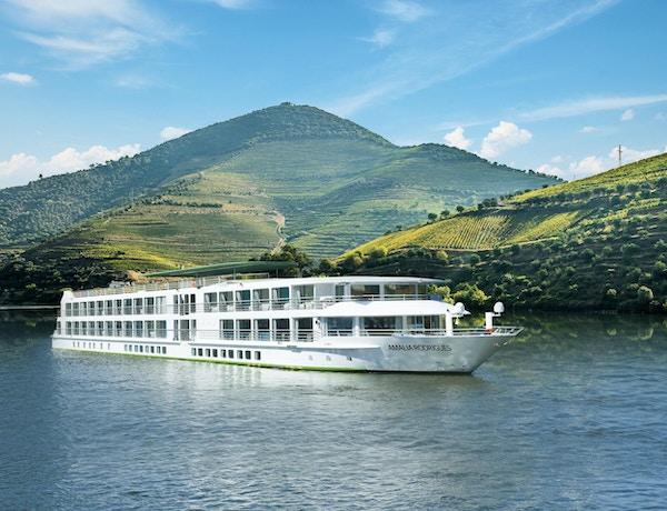 Skip som seiler på Douroelven langs grønne vinranker. Foto.