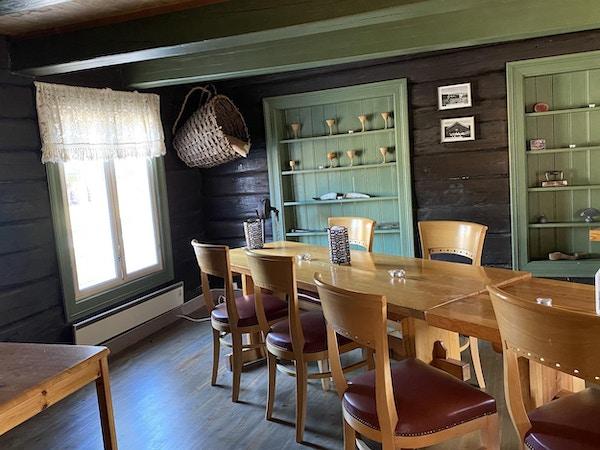 Bord med stoler og hyller med gamle pyntegjenstander samt en kurv som henger på veggen