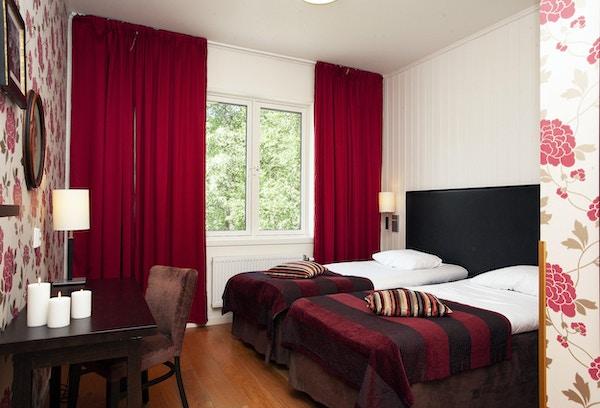 Hotellrom med tapet i røde fargetoner, stol, bord, seng og gardiner