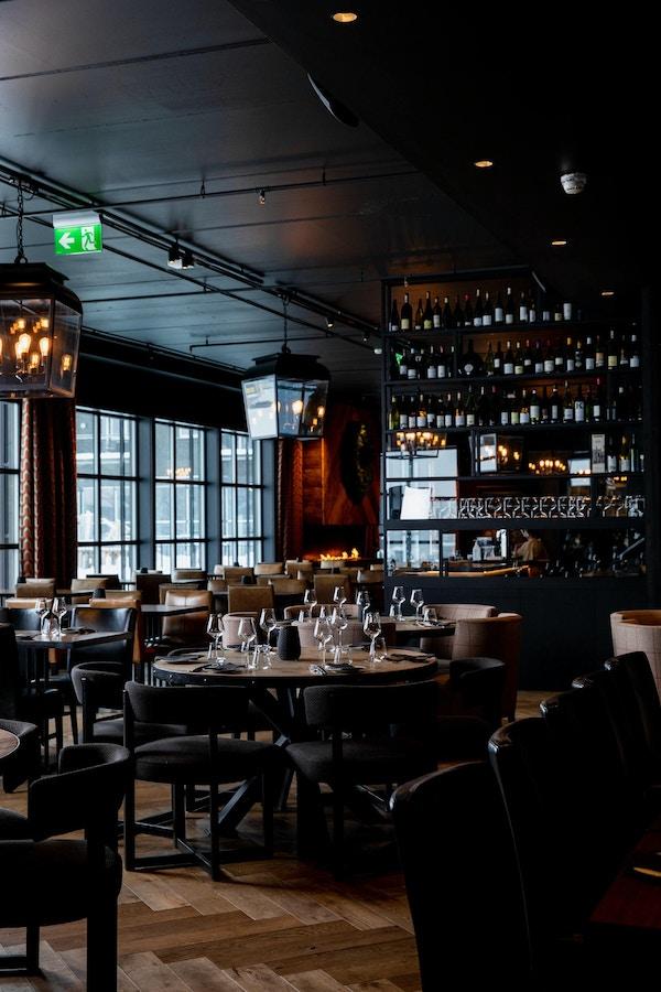 Bordene er dekket med dekketøy i en restaurant med bord og stoler og flotte lamper hengene fra taket